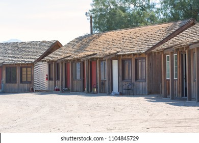 row of wooden house with space infront of motel with blue sky