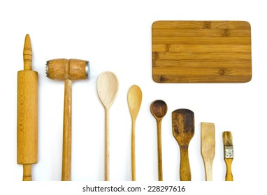 row of wooden kitchen utensils with a cutting board