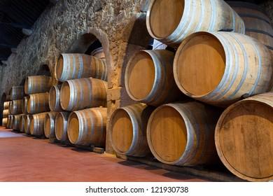 Row of wooden porto wine barrels in wine cellar (Porto, Portugal)