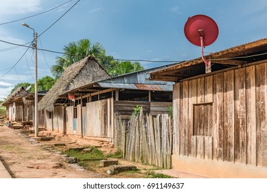 Row of wooden shacks with thatched roofs in Amazon village