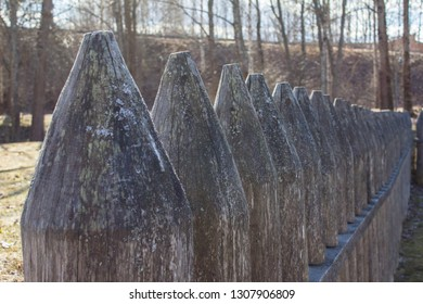 A row of wooden wide stakes in the backlight of the sun, an ancient fence in the park in Lappeenranta, Finland. Bright sin light and stockade, palisade, paling.