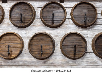 A row of wooden wine barrels built into a wooden wall. Wine cellar. Wine on tap.
