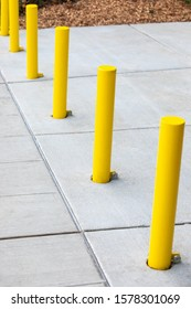 Row of yellow bollard poles along a concrete sidewalk