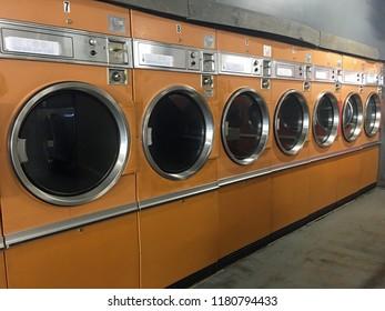 Row of yellow dryers in retro laundromat