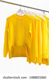 Row of yellow leather handbag with yellow clothes ,sweater, long shirt ,sundress,coat on a hanger,