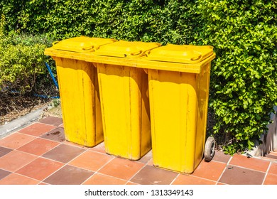 Row of yellow plastic trash bin for wate separation and recycling on green leaf background
