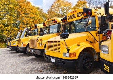 Row of yellow school buses against autumn trees