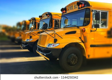 Row of yellow school buses parked inline with blurred background and sky reflecting off of windshields