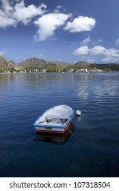 Rowboat anchored in lagoon with hills in background and blue sky and clouds