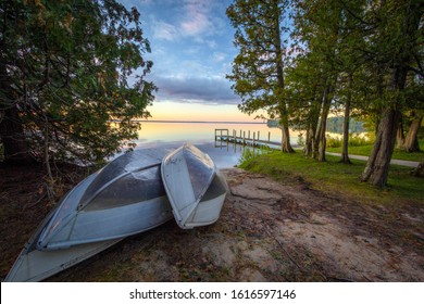 Rowboats On Sunset Lake. Group of aluminum rowboats on the beach of a sunset lake with a wooden dock in the background. Indian Lake State Park, Manistique, Michigan, USA.