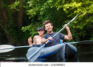 Rowers in boat sail along river and row oars on summer day. Sports guys are rafting down river. Leisure. Group of kayakers. Sports emotions of young man in boat with oar. Guys swim in canoe on water