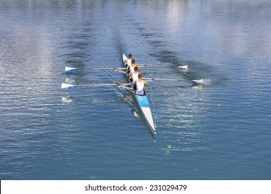 Rowers in four-oar rowing boats on the tranquil lake