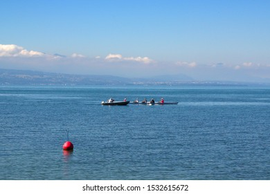 Rowers in a rowing boat are being coached and instructed at the Lake Geneva, Switzerland, probably this activity is a rowing class or lesson.