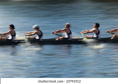Rowers in a rowing boat pulling in harmony, motion blurred to accent speed