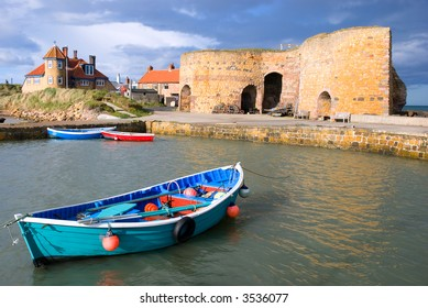 Rowing boat in Beadnell, Northumberland harbour overlooked by lime kilns