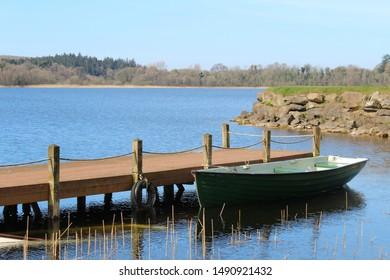 rowing boat beside jetty on lake