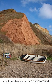 A rowing boat and fishing tackle at the base of the sandstone cliffs of the Jurassic era rising from Salcombe Regis beach