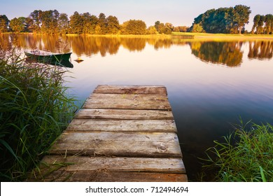 Rowing boat floating over calm waters. Early morning. Masuria, Poland.
