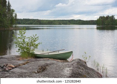 Rowing boat moored on the lake in the woods (Finland)