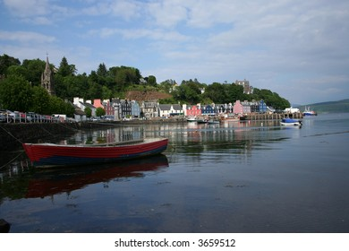 Rowing boat in tobermory harbour with colourful houses Mull Scotland