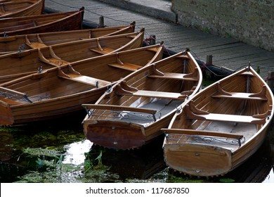 Rowing boats moored on a river in early morning light