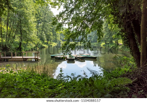 Rowing boats on a mountain lake with wooden pier in a wooded valley