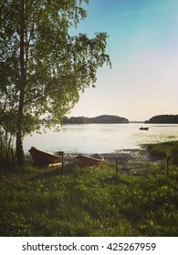 Rowing boats under a birch tree. Fisherman fishing in a boat in the background. Image has a vintage effect applied.