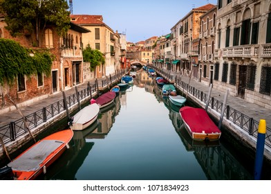 Rowing colourful gondolas in the back canal of Venice city