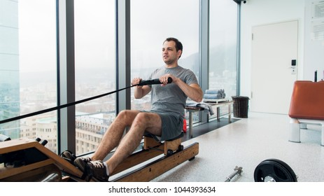 Rowing with power. Side view of young man in sportswear doing rowing in front of window at gym.