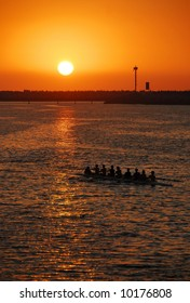 A rowing team returns from training during a golden sunset