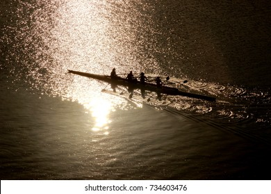 Rowing team working out on a sunrise