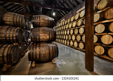 Rows of alcohol barrels in stock. Distillery. Cognac, whiskey, wine, brandy. Alcohol in barrels