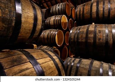 Rows of alcohol barrels in stock. Distillery. Cognac, whiskey, wine, brandy. Alcohol in barrels
