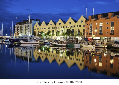 Rows of apartments, flats and marina in the regenerated Galway docklands illuminated at dusk