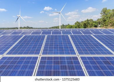 Rows array of poly crystalline silicon solar panels and wind turbines generating electricity in hybrid power plant station alternative renewable energy from natural with  blue sky