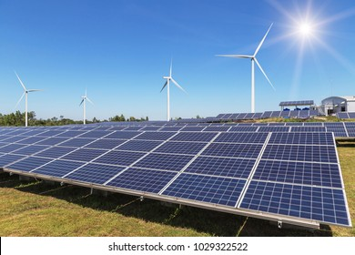 Rows array of  polycrystalline silicon solar panels and wind turbines generating electricity in hybrid power plant systems station alternative renewable energy from natural with blue sky background