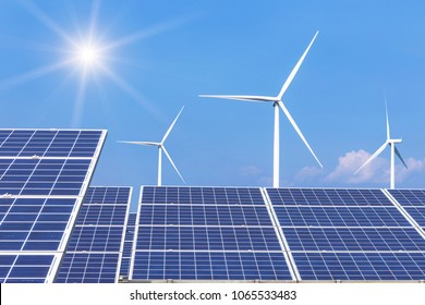 Rows array of  polycrystalline silicon solar panels and wind turbines generating electricity in hybrid power plant systems station alternative renewable energy from natural with blue sky