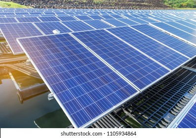 rows array of polycrystalline silicon solar cells or photovoltaics in solar power plant floating on the water in lake