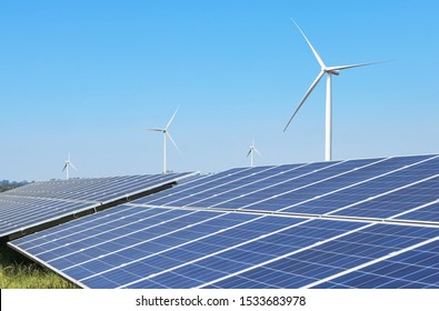 Rows array of solar cells or photovoltaic cells with wind turbines generating electricity alternative renewable wind energy and sunlight energy in hybrid power plant station with blue sky