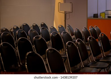 Rows of black chairs with billboard background