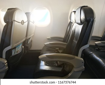 Rows of black leather seats and illuminator windows down the aisle in commercial aircraft cabin. Economy class chairs of airplane. Background, copy space, close up.