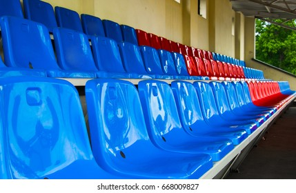 Rows of blue and red seats on an empty sports platform