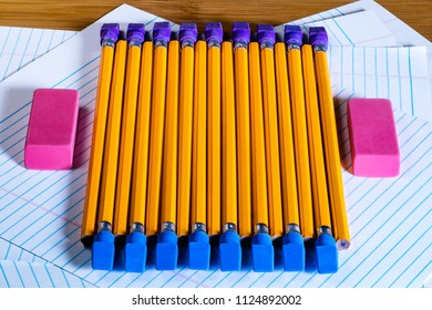 Rows of brightly colored pencil erasers lined up in an OCD orderly fashion, with pencils laying across them. High contrast lighting, high vibrancy with a shallow depth of field