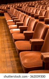 Rows of brown theater seats in a concert hall