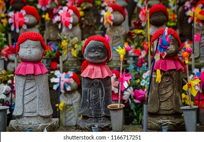 Rows Buddhist Jizo Statues with Red Bibs, Hats, Scarves, Flowers, and Toy Fans. Religious Stone Children Statues (Tokyo, Japan).