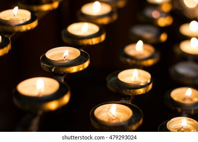 Rows of candles in a church that have been lit by worship in remembrance of loved ones.