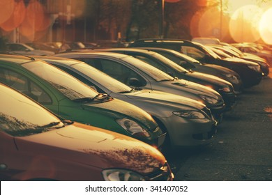 Rows of cars parked in residential district in sunset, retro toned image with lens flare and bokeh light, selective focus
