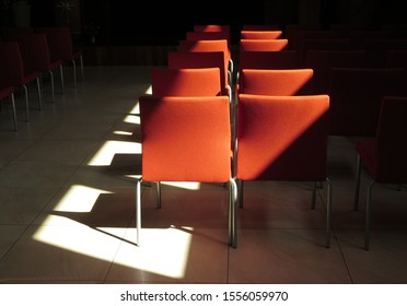 Rows of chairs, with the afternoon sunlight, shining through windows,  spotlighting some of them