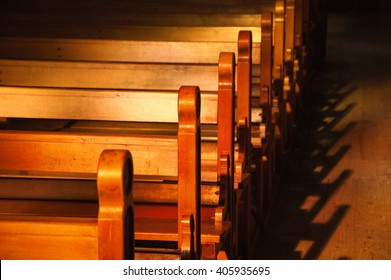 Rows of church benches. Sunlight filtered through the stained glass window. Selective focus.