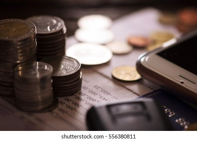Rows of coins, account book, mobile, credit card and car key remote. Finance and banking concept.